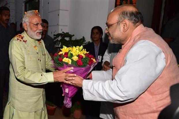 "BJP chief Amit Shah welcomes Modi at the party headquarters to celebrate the victory in UP and Uttrakhand Assembly elections, in New Delhi on Sunday. ""Results in five states will takes the BJP forward from its historic win in 2014 general elections"", said Shah in his address to party workers."