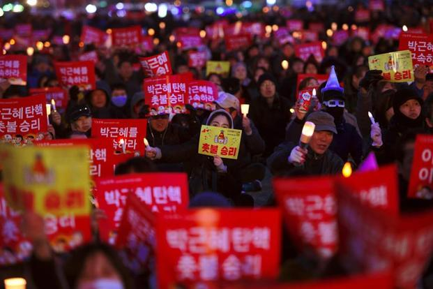 South Korean demonstrators hold up red banners reading 'Park Geun-Hye impeachment, candlelight victory!' during a candlelit rally demanding arrest of the impeached-president in Seoul on Friday. Photo: AFP