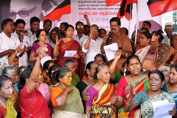 DMK president M. Karunanidhi's daughter and party MP Kanimozhi along with party workers staging a protest outside a ration shop against state govenment demanding adequate supply of commodities, in Chennai on Monday. Photo: PTI