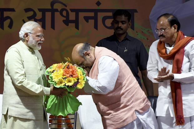 Prime Minister Narendra Modi greets BJP president Amit Shah at the party headquarters to celebrate the party's victory in Uttar Pradesh and Uttarakhand assembly elections in New Delhi on Sunday. Photo: PTI