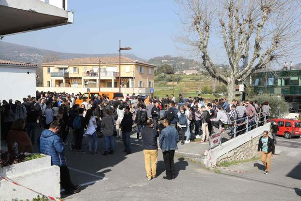 People gather near the Tocqueville high school in the southern French town of Grasse, on Thursday following a shooting that left eight people injured. Photo: AFP