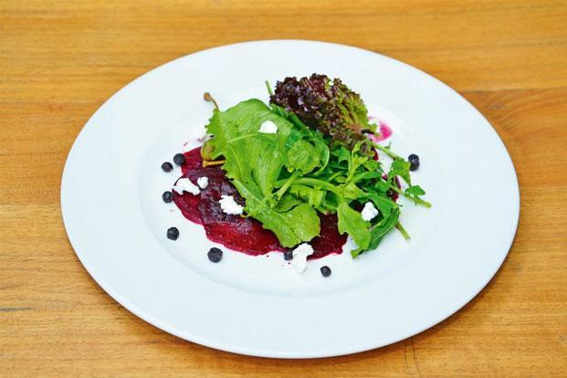 Boiled beetroot salad with berries and garden greens