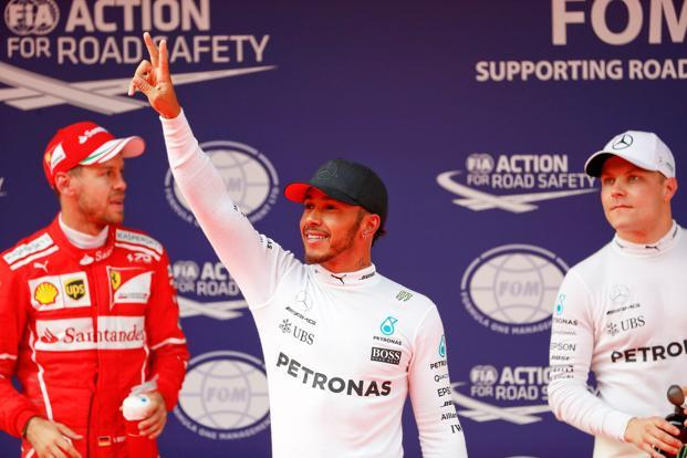 Mercedes driver Lewis Hamilton (C) reacts after setting pole position in qualifying alongside team mate Valtteri Bottas (R) and Ferrari's Sebastian Vettel at the Shanghai International Circuit in China. Photo: Reuters