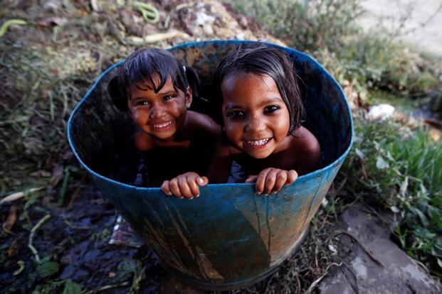 Girls bath inside a drum to beat the heat at a field in New Delhi on Tuesday. Adnan Abidi/Reuters
