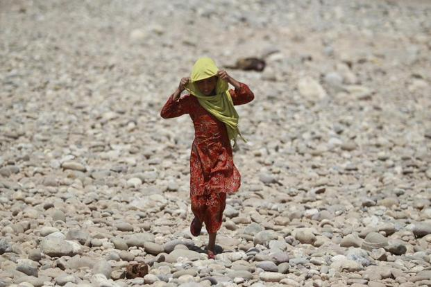 A young girl covers her face to protect from the heat as she walks on the dried bed of the River Tawi, Jammu. Channi Anand/AP.