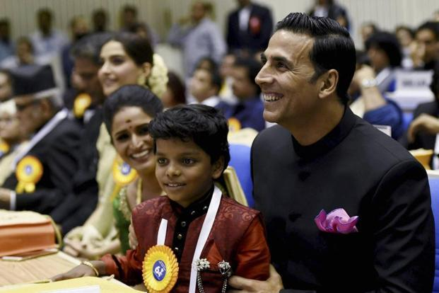 Akshay Kumar, Surabhi C.M. and child actor Adish Praveen, who won the Best Child Artist award for his role in 'Kunju Daivam', during the 64th National Film Awards in New Delhi. PTI