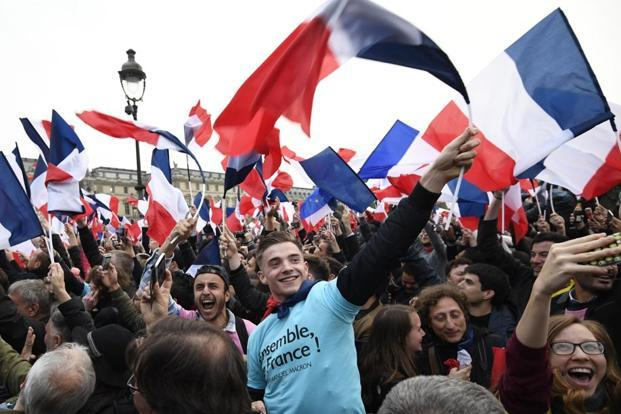 Supporters of president-elect Emmanuel Macron wave French national flags as they celebrate in front of the Pyramid at the Louvre Museum in Paris on 7 May, 2017. Eric Feferberg/AFP