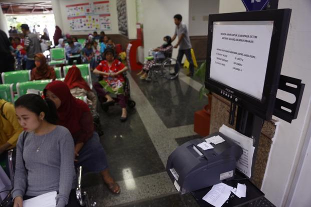 "Patients wait near a queue number dispenser affected by the ""WannaCry"" ransomware cyber attack at Dharmais Cancer Hospital in Jakarta on Monday. Photo: Dita Alangkara/AP"