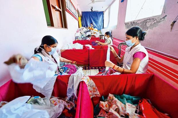 Staffers at non-profit Goonj make sanitary pads from donated clothes. Photograph: Priyanka Parashar/Mint