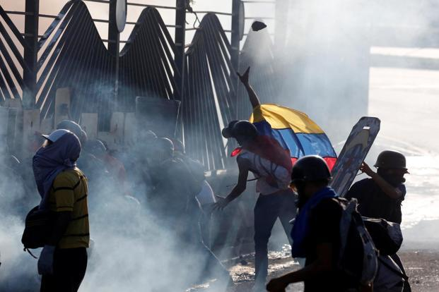 Opposition supporters clash with riot security forces during a rally against Venezuelan president Nicolas Maduro in Caracas on Thursday. Photo: Reuters