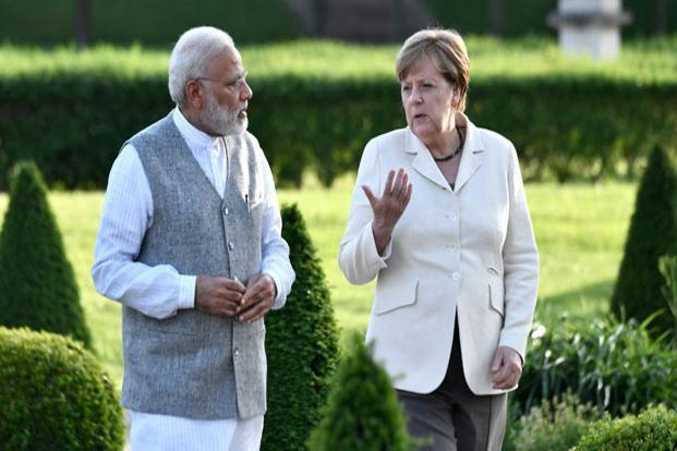 German Chancellor Angela Merkel (R) and Indian Prime Minister Narendra Modi take a walk in the garden prior to consultations at the Mesberg palace near Berlin. John MacDougall/AFP