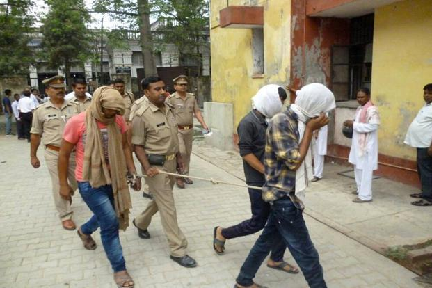 Police escort three suspects arrested in connection with a video posted on social media showing a sexual assault at the district court in Rampur on 29 May. Photo: AFP