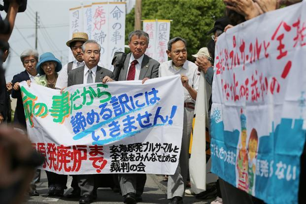 Residents seeking to suspend the operation of No.3 and No.4 reactors of Genkai nuclear plant hold a banner on 13 June. Photo: AFP