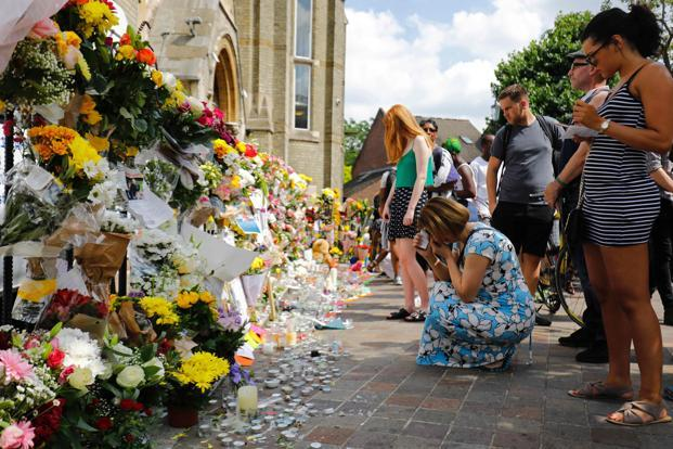 People look at floral tributes outside the Notting Hill Methodist Church, left for the victims of the June 14 Grenfell Tower block fire, in Kensington, west London. Photo: AFP
