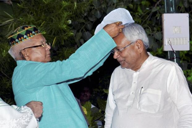 Bihar chief minister Nitish Kumar is offered a cap by RJD chief Lalu Prasad at a