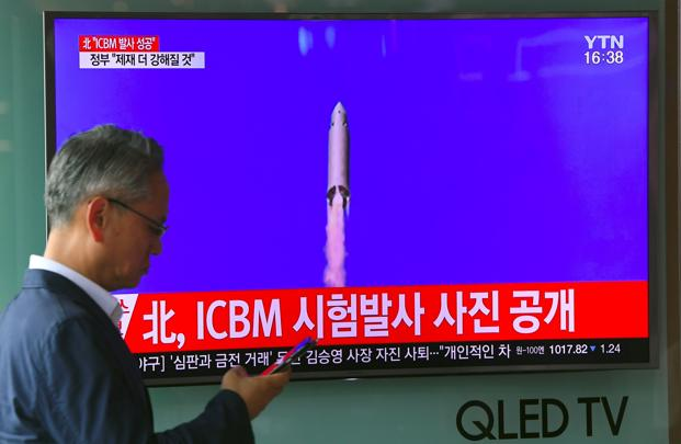 A man walks past a television screen showing a picture of North Korea's test launch of an ICBM, at a railway station in Seoul on 4 July 2017. Photo: AFP
