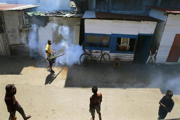 A Sri Lankan municipal worker fumigates during dengue fever irradiation work in Colombo, on Tuesday. Photo: AP
