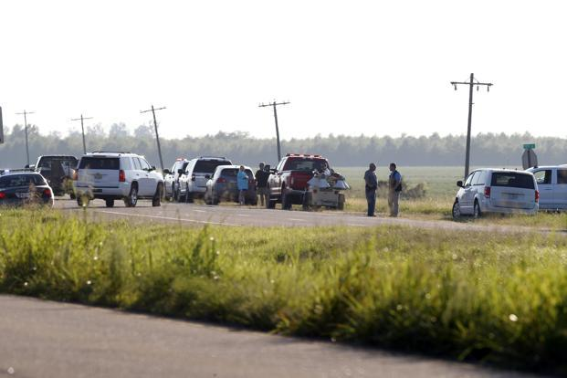 Emergency personnel stand along US Highway 82 after a military transport plane crashed into a field near Itta Bena, Miss., on the western edge of Leflore County. Photo: AP