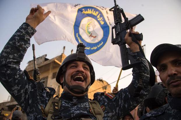 Members of the Iraqi forces celebrate after defeating Islamic State group fighters in the decisive battle for Mosul on Monday. Photo: Fadel Senna/AFP