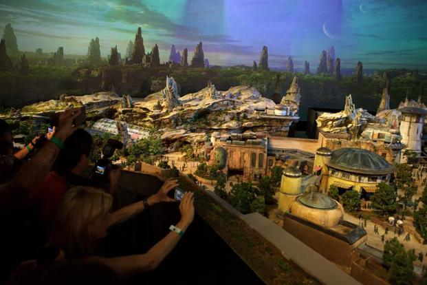 Attendees take photographs of the 3D model of Disney's Star Wars lands, unveiled ahead of the D23 Expo in Anaheim, California, on Thursday. Photo: Troy Harvey/Bloomberg
