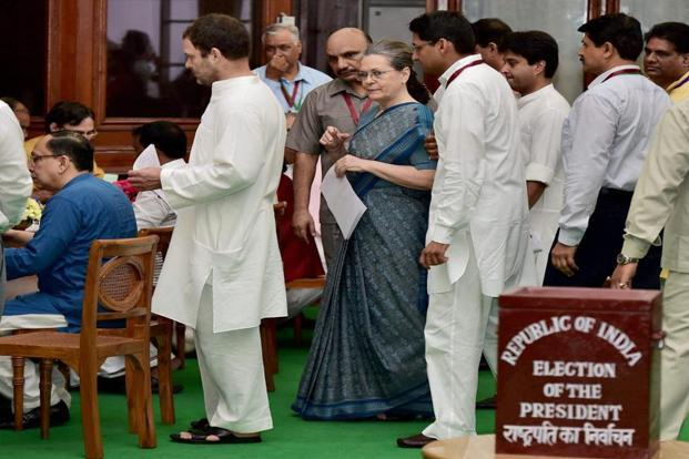 Congress president Sonia Gandhi (centre) with party vice president Rahul Gandhi wait to cast their votes, in New Delhi on Monday. PTI
