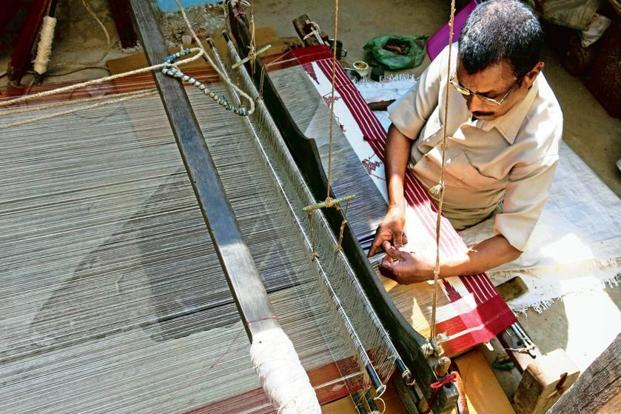 "Gobardhana Panika works on his pit loom. ""If others do not learn, we will end up as the last generation of Kotpad weavers,"" he says."