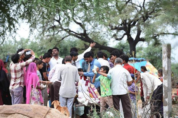 Villagers affected by the floods gather to get food aid distributed by an NGO at Jasra village, Gujarat, on Saturday. AFP