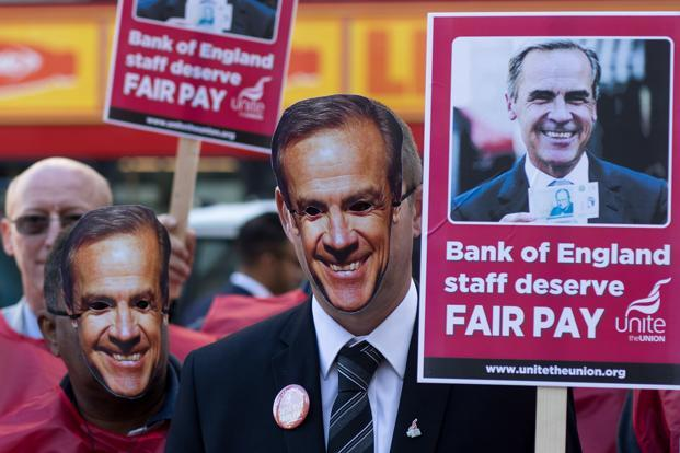 Bank of England employees wear masks depicting the bank's governor Mark Carney during a strike in London on Tuesday. Photo: Simon Dawson/Bloomberg