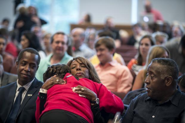 School president Donna Harris hugs ninth-grader Alexis Stanley as she arrives at a prayer service at the Minnehaha Academy Lower School on Wednesday. Photo: AP