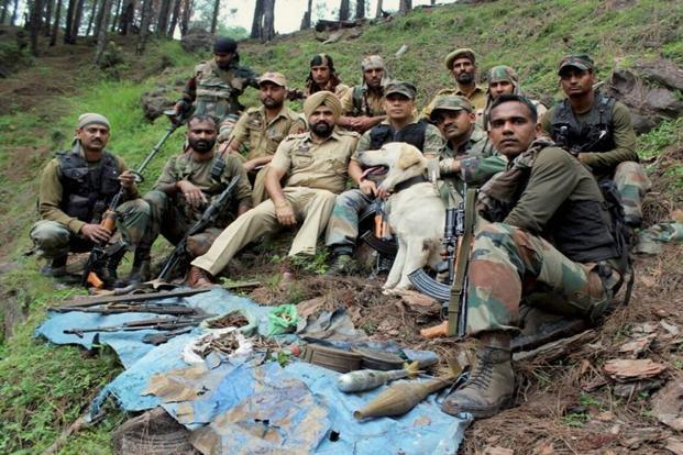 Army and J&K police men showing a huge cache of arms and ammunition, including two AK assault rifles and explosives, seized during a joint operation in Rajouri on Sunday. Photo: PTI