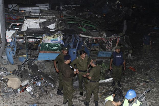 Pakistani security personnel visit the site of a blast in Lahore on Monday. Photo: AP