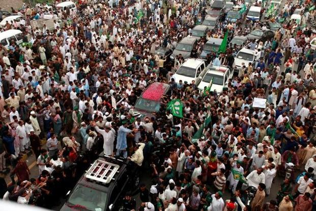Supporters of former Pakistani prime minister Nawaz Sharif crowd around his car as his convoy enters Rawalpindi, Pakistan on 9 August 2017. Photo: Faisal Mahmood/Reuters