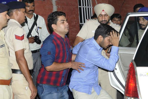 Vikas Barala (in blue shirt) being taken into Chandigarh police custody at Sector 26 police station on Wednesday. Photo: Hindustan Times
