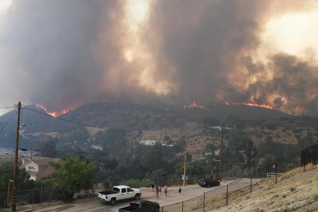 People watch as flames from the La Tuna Fire blaze on a hill in the Shadow Hills neighborhood of Los Angeles, California. Photo: AFP