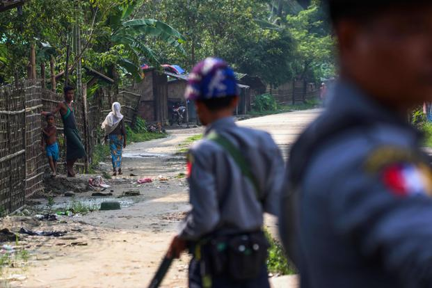 Rohingya Muslims in the village of Shwe Zarr as Myanmar policemen stand guard, near Maungdaw township in Rakhine state on Wednesday. Photo: AFP
