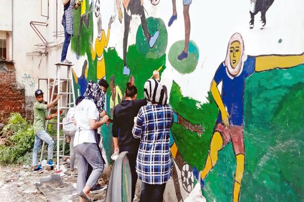 The Khirki Collective creating a wall painting of girls playing football in a public space. Photo: Revue/Khirki Collective
