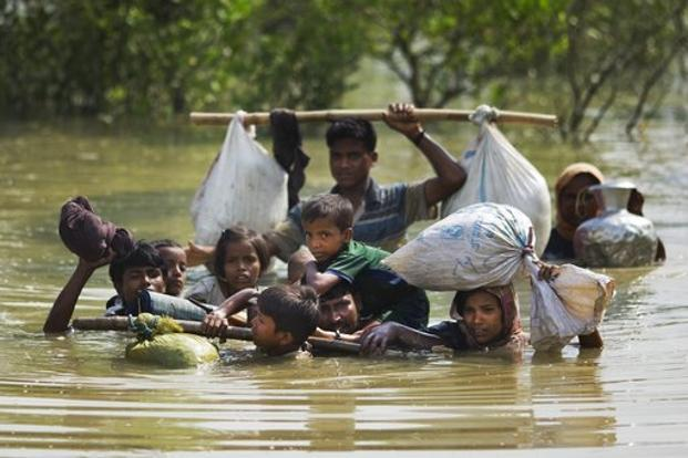 A Rohingya family reaches the Bangladesh border after crossing a creek of the Naf river on the border with Myanmmar. Photo: AP