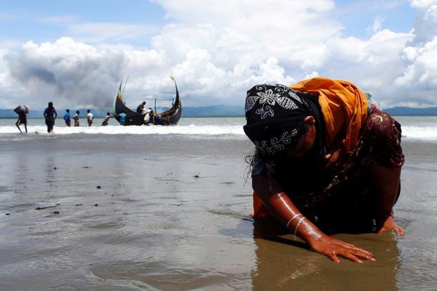 An exhausted Rohingya refugee touches the shore after reaching Bangladesh by boat, in Shah Porir Dwip, Bangladesh, on Monday. Photo: Danish Siddiqui/Reuters