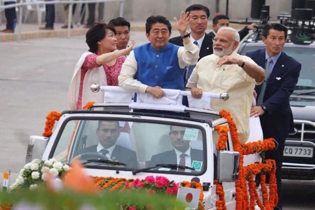 Prime Minister Narendra Modi, Japanese Prime Minister Shinzo Abe and his wife Akie Abe wave from an open vehicle during their roadshow in Ahmedabad on Wednesday. Photo: PTI
