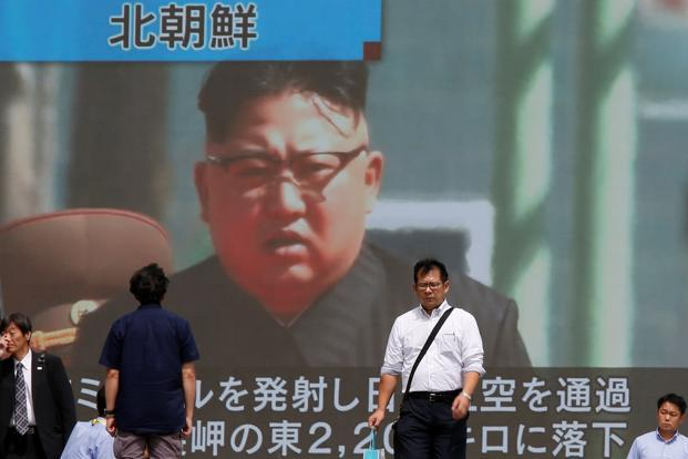 Passers-by walk past a TV screen reporting news about North Korea's missile launch in Tokyo on Friday. Photo: Reuters