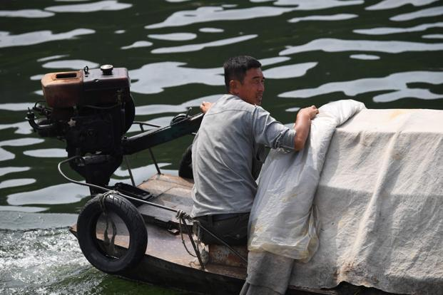 A North Korean man brings his boat up to a Chinese tourist boat to sell North Korean products, on the Yalu river near the North Korean town of Sinuiju, opposite the Chinese border city of Dandong on 4 September 2017.  Photo: AFP