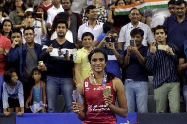India's Pusarla V. Sindhu poses with gold medal and trophy during the awards ceremony after winning against Japan's Nozomi Okuhara during women's single final match at the Korea Open Badminton in Seoul, South Korea. Photo: AP