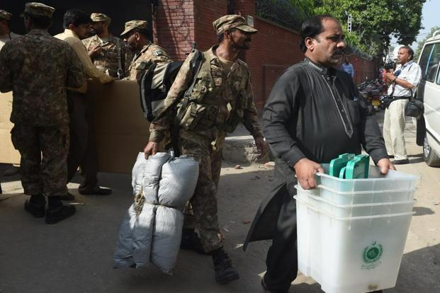 Pakistani army soldiers help a polling officer carry election materials received from the election commission office in Lahore on 16 September 2017, for the by-election of the parliamentary seat held by Nawaz Sharif. Photo: AP