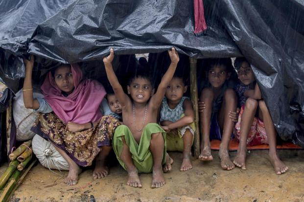 A Rohingya Muslim family, who crossed over from Myanmar into Bangladesh, takes cover under a plastic sheet as it rains near Balukhali refugee camp, Bangladesh, on 17 September 2017. Photo: AP/Dar Yasin
