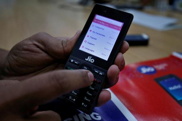 A sales person displays features of JioPhone as he poses for a photograph at a store of Reliance Industries' Jio telecoms unit, on the outskirts of Ahmedabad on Tuesday. Photo: Amit Dave/Reuters