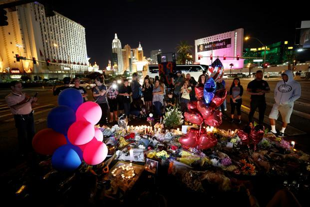 People gather at a makeshift memorial in the middle of Las Vegas Boulevard to mark the mass shooting in Las Vegas, Nevada, on Wednesday. Photo: Reuters (Reuters)