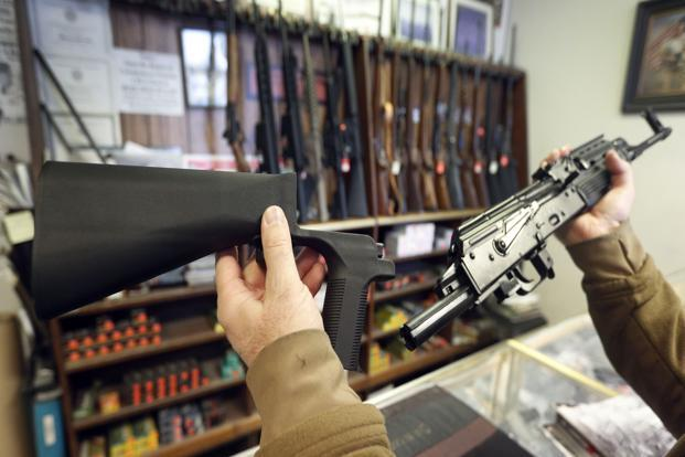 A bump stock device (left) that fits on a semi-automatic rifle to increase the firing speed is shown next to a AK-47 (right) at a gun store on Thursday in Salt Lake City, Utah. Congress is talking about banning this device after it was reported to have been used in the Las Vegas shootings. Photo: AFP (AFP)