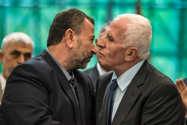 Fatah's Azam al-Ahmad (right) and Saleh al-Aruri of Hamas kiss after signing a reconciliation deal in Cairo on Thursday.  Photo: AFP