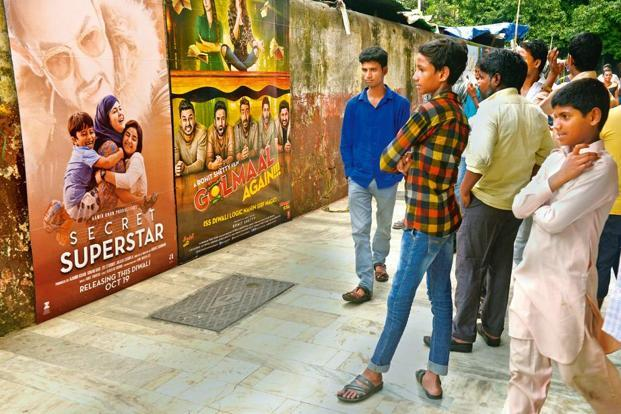 Passers-by outside Maratha Mandir theatre look at the posters of this year's Diwali releases, 'Secret Superstar' and 'Golmaal Again!!!'. Photo: Abhijit Bhatlekar/Mint