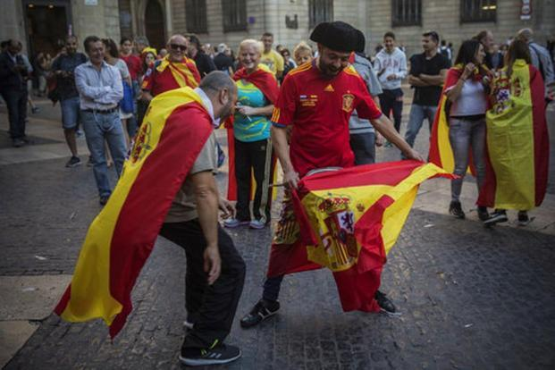 Men perform a bullfighting game outside the Palau Generalitat after a mass rally against Catalonia's declaration of independence. AP